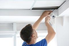 Technician installing CCTV camera. On ceiling indoors Stock Photos