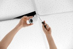 Technician installing CCTV camera. On ceiling indoors Royalty Free Stock Photography