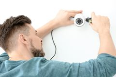 Technician installing CCTV camera. On wall indoors Royalty Free Stock Images