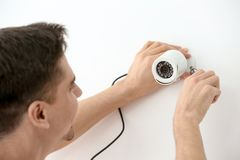 Technician installing CCTV camera on wall indoors. Professional technician installing CCTV camera on wall indoors Stock Images