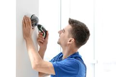 Technician installing CCTV camera on wall indoors. Professional technician installing CCTV camera on wall indoors Stock Photography