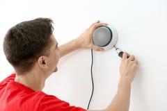 Technician installing CCTV camera. On wall indoors Stock Photography