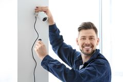 Technician installing CCTV camera. On wall indoors Stock Photo