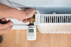 Technician installing digital thermostat Stock Images