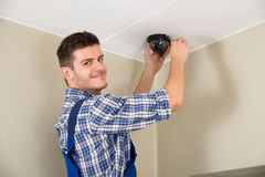 Technician Installing Surveillance Camera. Young Male Technician Installing Surveillance Camera On Ceiling Royalty Free Stock Photo