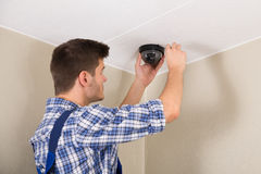 Technician Installing Surveillance Camera. Young Male Technician Installing Surveillance Camera On Ceiling Royalty Free Stock Photos