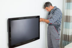 Technician Installing Television At Home