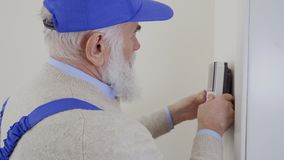 Technician installs intercom on the wall. Mature specialist install the intercom on the wall. Old man wearing protective coveralls works as hired worker in stock footage