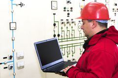Electrician with laptop reading instruments in power plant control center stock photo