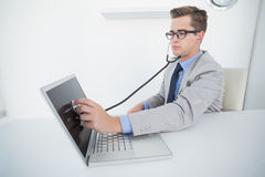 Technician listening to laptop with stethoscope Stock Photo