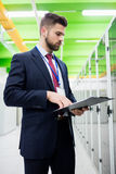 Technician looking at clipboard. In server room Stock Photos