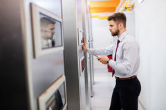 Technician looking at server cabinet. In server room Stock Photo