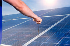 Technician maintaining  solar panels. Photovoltaic system with solar panels for the production of renewable energy through solar energy, a technician using a Royalty Free Stock Image