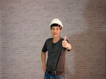 Technician man ware white helmet with dark grey T-shirt and denim jeans standing and left hand thumbs up. Technician man ware white helmet with dark grey T Stock Photo