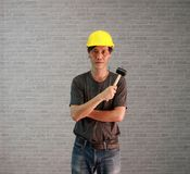 Technician man ware yellow helmet with dark grey T-shirt and denim jeans standing and hugging chest with rubber hammer in hand. royalty free stock photo