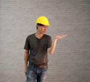 Technician man ware yellow helmet with dark grey T-shirt and denim jeans standing and palms facing up of left hand. Technician man ware yellow helmet with dark Royalty Free Stock Photos