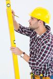 Technician marking while using spirit level Stock Image