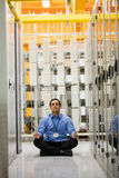 Technician meditating in hallway. Of server room Royalty Free Stock Images