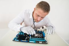 Technician With Motherboard And Stethoscope Royalty Free Stock Photo