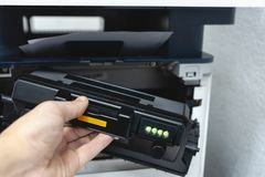 Technician office worker fixing photocopy machine with replacement toner cartridge. refilling cartridge with toner for printing do stock photography