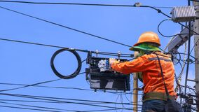 Free Technician On Wooden Ladder Is Working To Install Fiber Optic And Splitter Box On Power Pole Against Blue Sky Stock Images - 197668214
