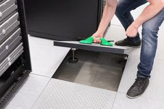 IT technician opens Datacenter Floor. A IT engineer / technician opens data floor. Shot in a datacenter Stock Photo