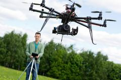 Technician Operating UAV Octocopter. UAV octocopter flying with technician operating in background at park Stock Image