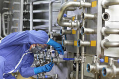 Technician in overalls maintaining technological system in plant. Technician in overalls mask, gloves and goggles  maintaining technological system in plant Royalty Free Stock Image
