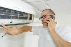 Technician on phone fixing air conditioning system. Technician on the phone fixing air conditioning system Stock Photos