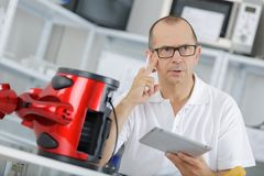 Technician on phone trying to fix vaccum cleaner. Technician on the phone trying to fix the vaccum cleaner Stock Photography