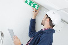 Technician placing emergency exit sign. Technician placing an emergency exit sign stock photos