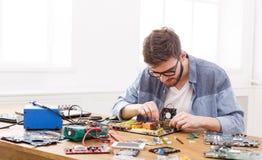 Technician plug in microprocessor to motherboard. Technician plug in CPU microprocessor to motherboard close up. Computer upgrade in service center stock photo