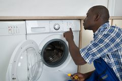 Technician Pressing Button On Washing Machine Royalty Free Stock Image