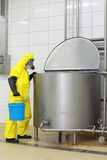 Technician in  protective  coveralls  with blue bucket at opened industrial process tank Royalty Free Stock Images