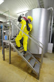 Technician in protective coveralls with sample of fluid Stock Image