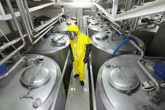 Technician in protective uniform checking technological process Stock Photos