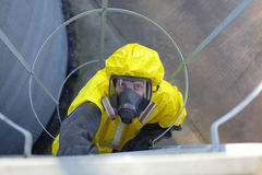 technician in protective uniform going up a metal  Stock Photos
