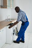 Technician Pulling Washing Machine In Kitchen Royalty Free Stock Image