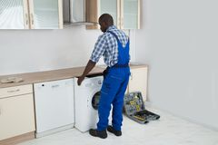 Technician Pulling Washing Machine In Kitchen Royalty Free Stock Photo