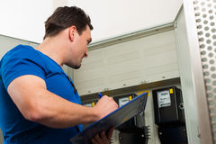 Technician reading the electricity meter Stock Photos