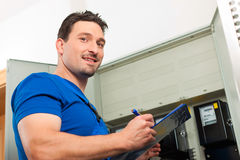 Technician reading the electricity meter Royalty Free Stock Photography