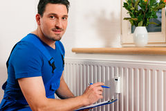 Technician reading the heat meter. To check consumption Royalty Free Stock Photo