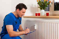 Technician reading the heat meter. To check consumption Stock Photos