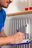 Technician reading the heat meter. To check consumption Stock Photo