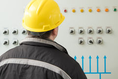 Technician reading instruments in power plant control center stock photos