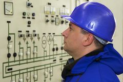 Engineer with red helmet control instruments in power plant royalty free stock photos