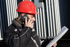 Technician in red helmet make call in power plant royalty free stock photo