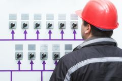 Technician with red helmet reading instruments power plant con. Engineer with red helmet reading instruments power plant control center royalty free stock image
