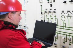 Technician in red with laptop reading instruments in power plant. Electrician in red with laptop reading instruments in power plant control center stock image
