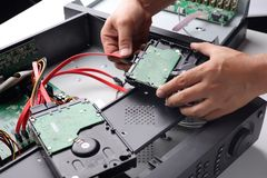 Technician remove a hard disk drive from the CCTV DVR recorder case , to install a new hard drive and upgrading to a Solid State. Drive SSD in to surveillance royalty free stock photography